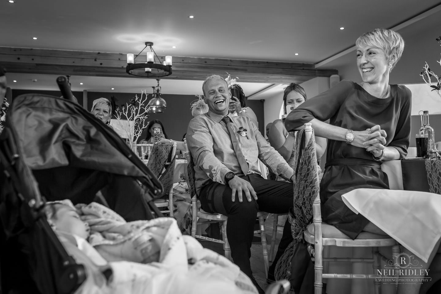 Black and white image of wedding guests during the wedding breakfast at The Mill at Conder Green