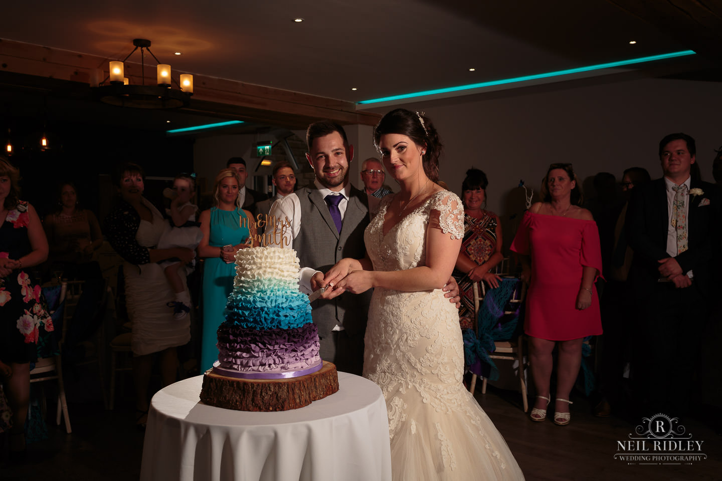 Bride and groom cut the cake on the dance floor at The Mill at Conder Green