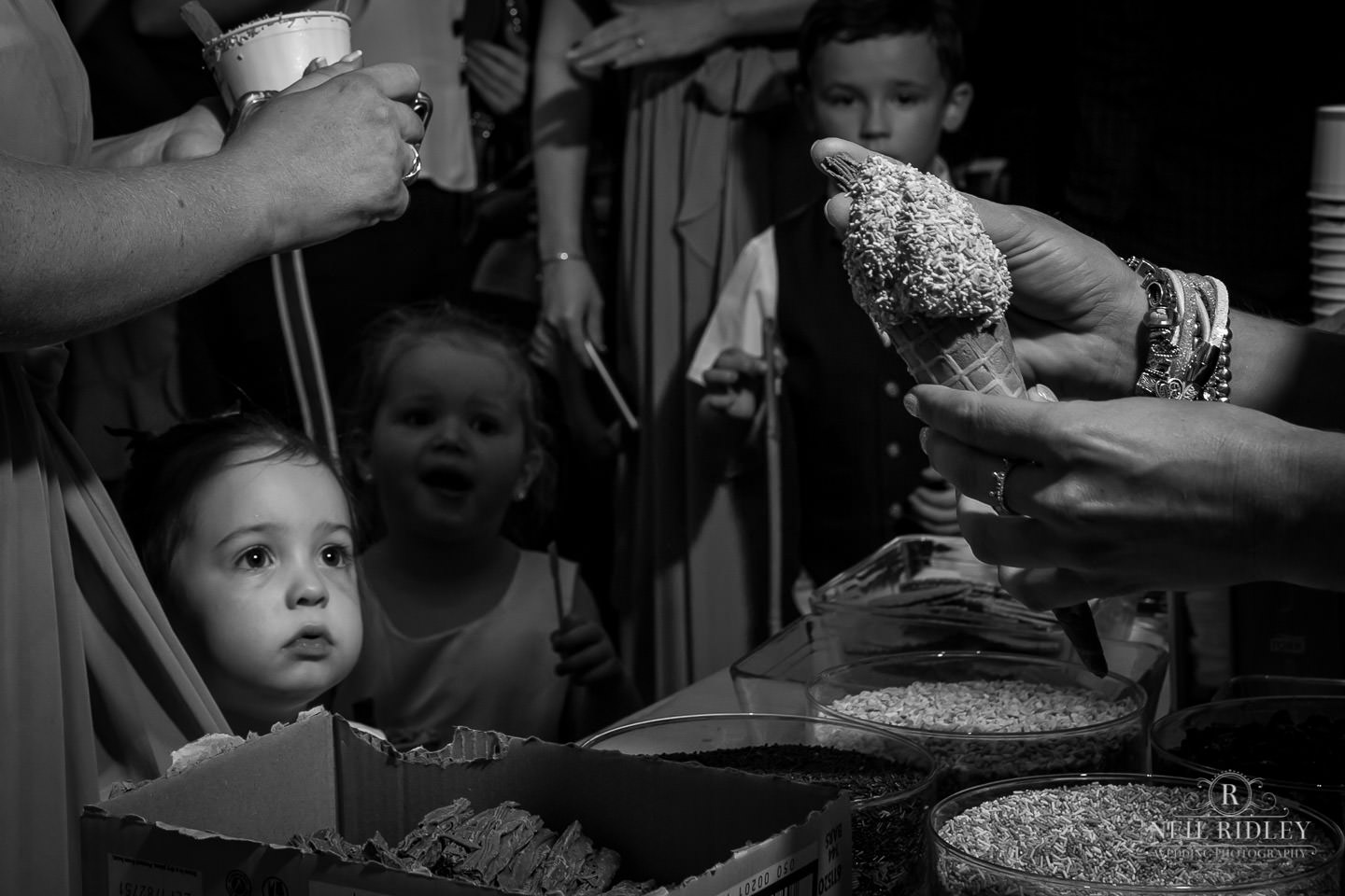 Black and white image of young bridesmaid having a ice cream at The Mill at Conder Green