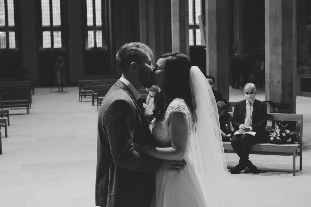 Couples first kiss in church,black and white wedding photgraphy, micro wedding