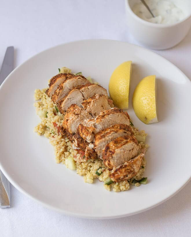 Cajun spiced oven baked chicken is a low cost, lean and tasty quick healthy meal. With a delicious bulgur wheat, tomato and cucumber side salad this recipe makes for an excellent mid-week dinner or lunch option!