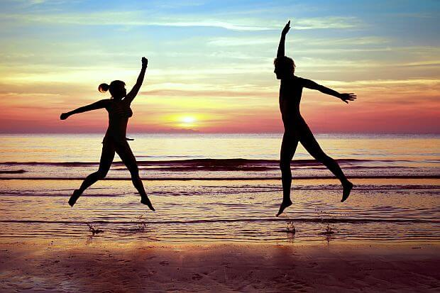 happy couple jumping on the beach, summer vacations