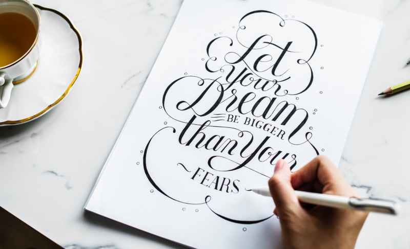 person writing calligraphy style quote on table