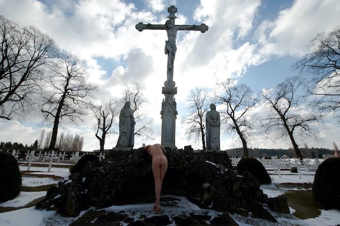 naakte vrouw aan Jezus kruis sneeuw
