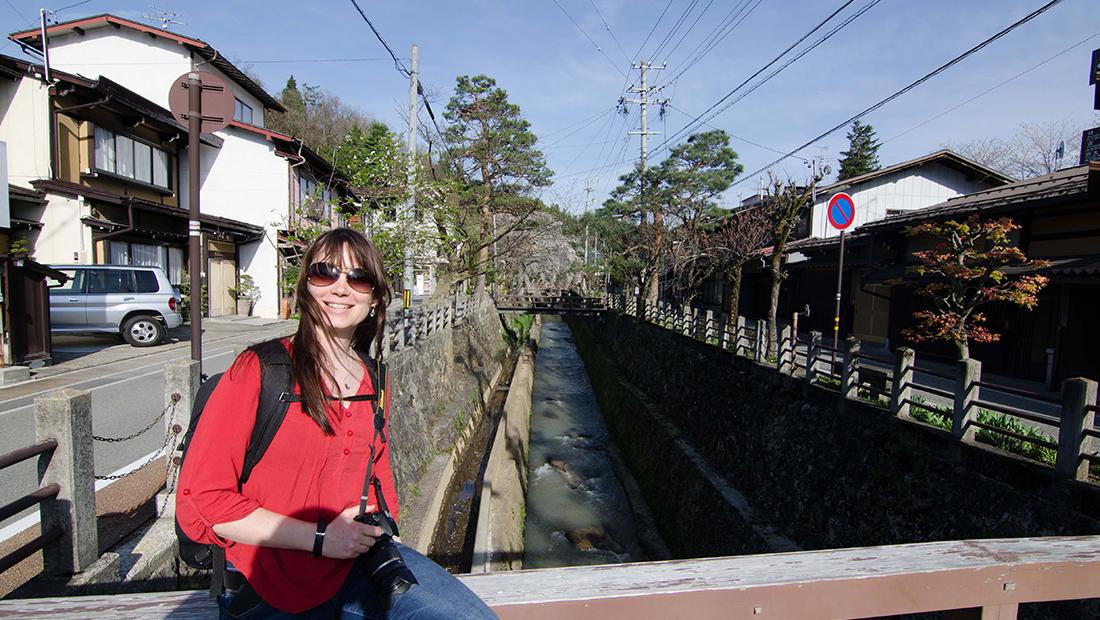 Nele auf einer Holzbrücke sitzend in Takayama, Japan