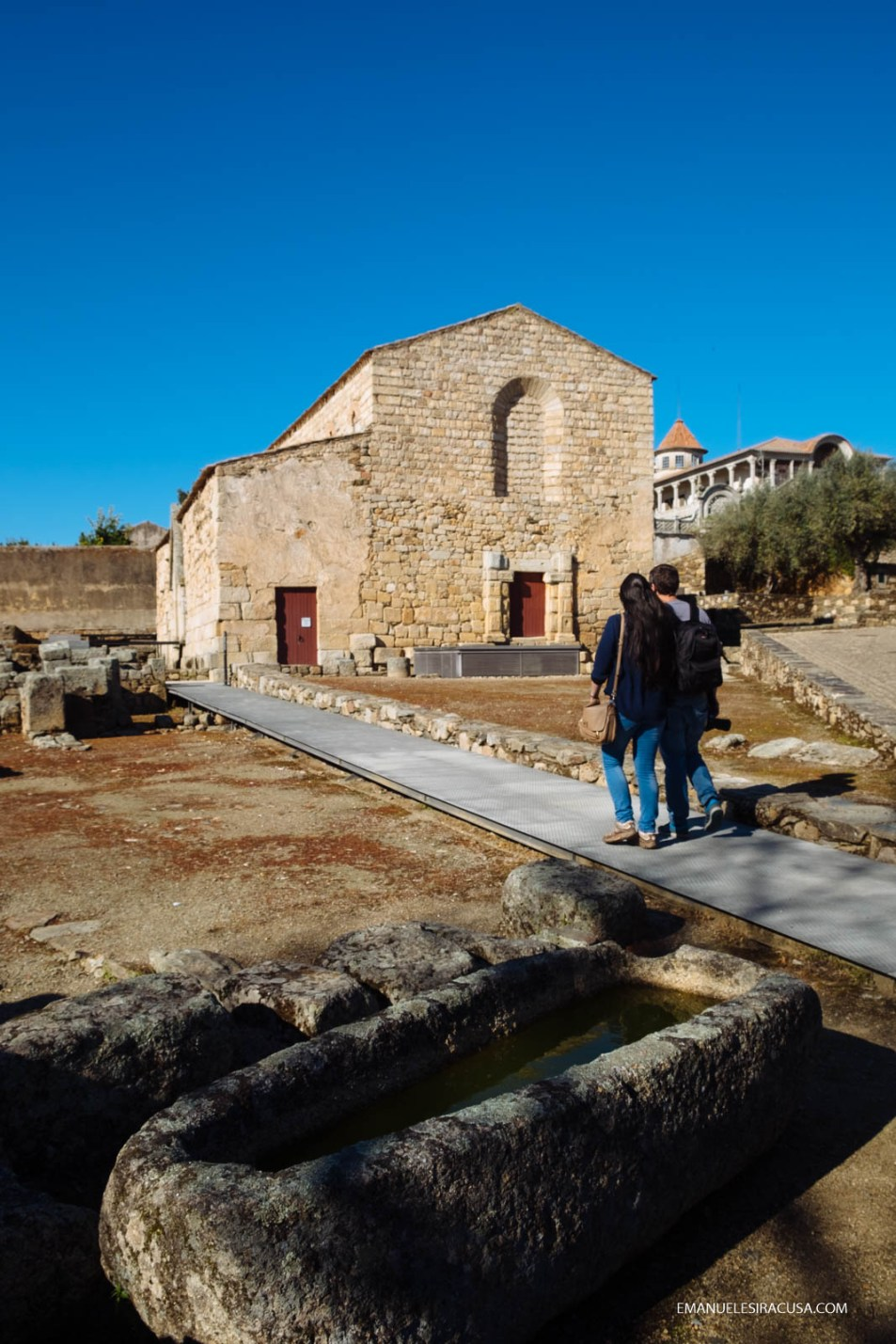 A couple of tourists walks by the Sé, Cathedral of Idanha a Velha, 2016