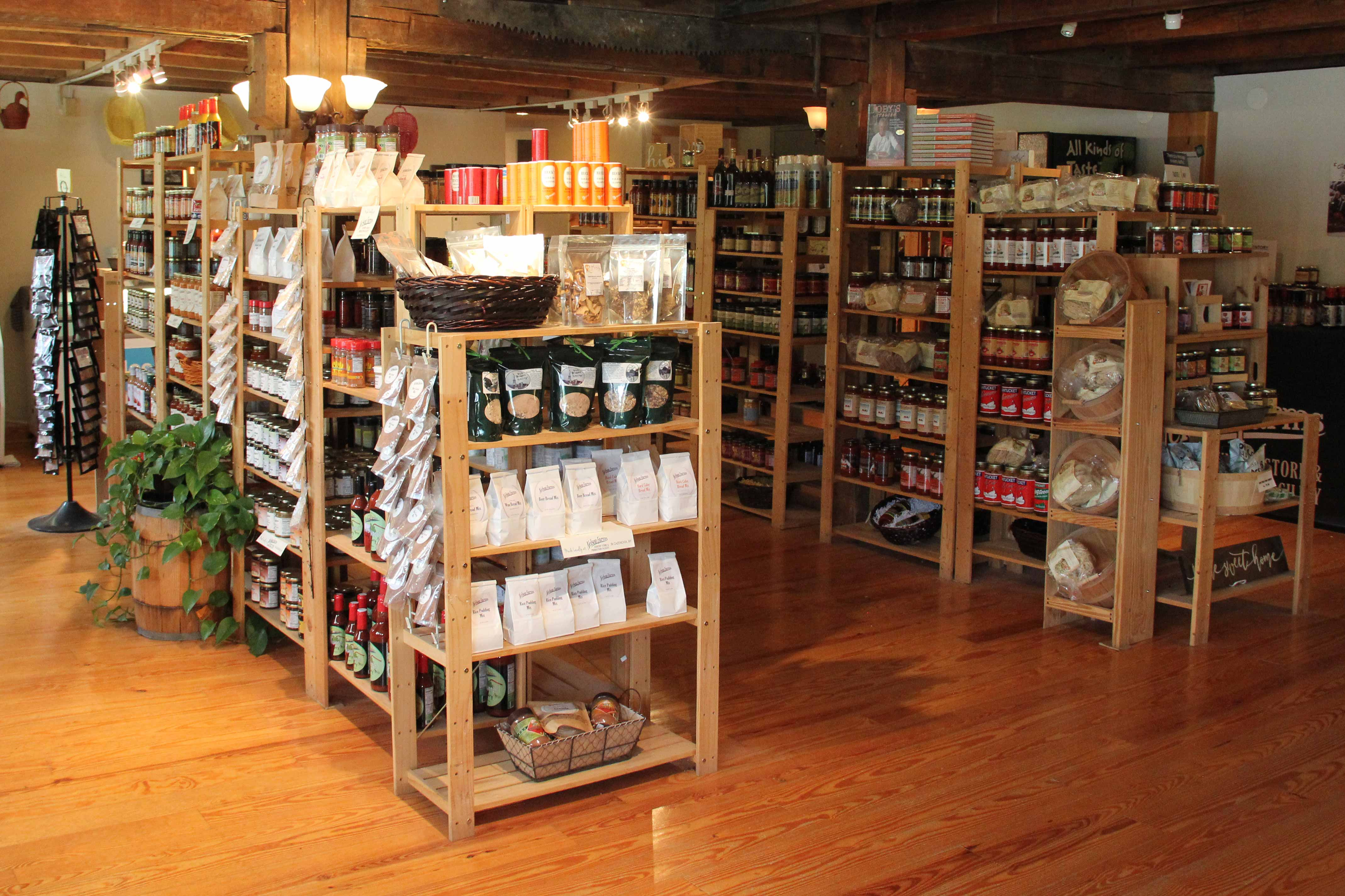 Photo of store interior. Wooden floors and wooden open shelving filled with products fill the room.
