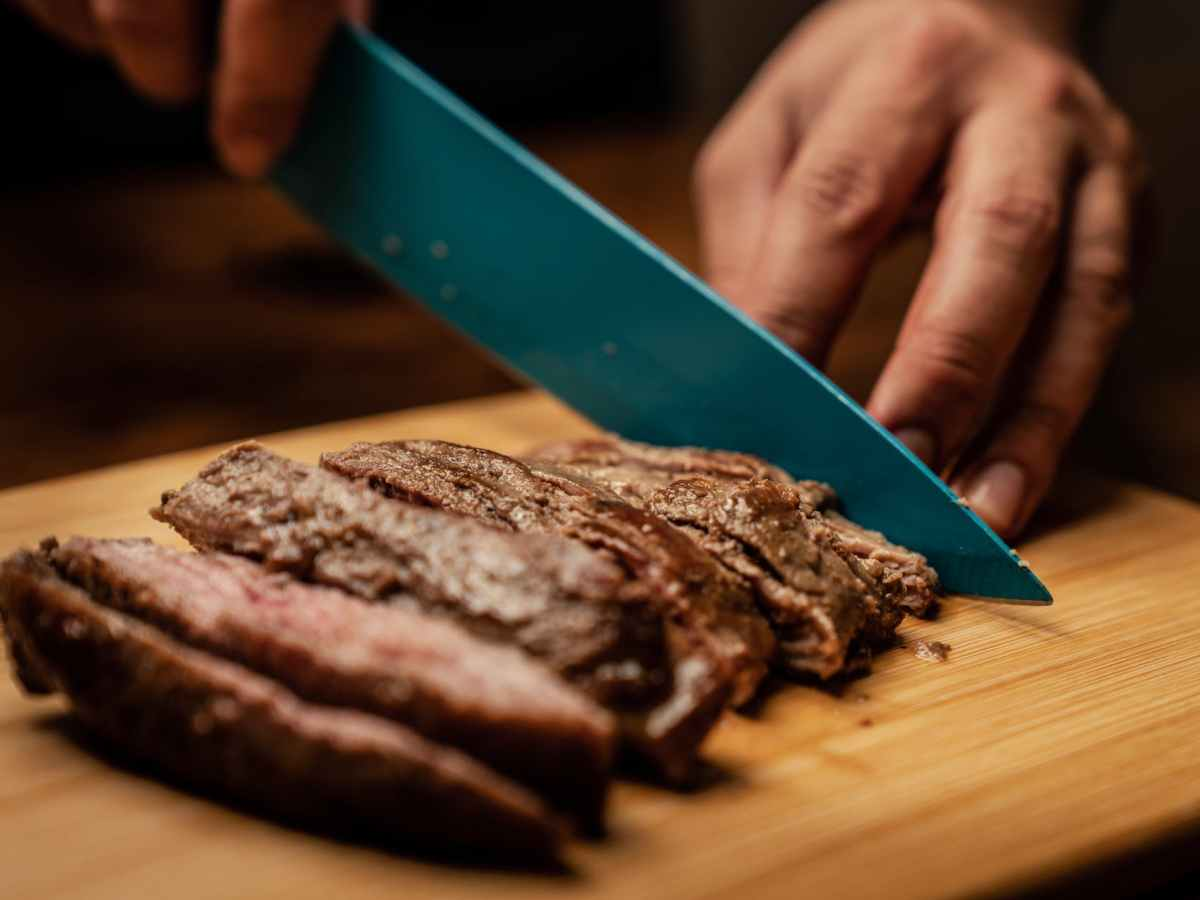 person slicing chocolate cake on green chopping board