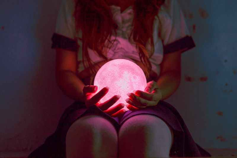 person holding ball night lamp while sitting