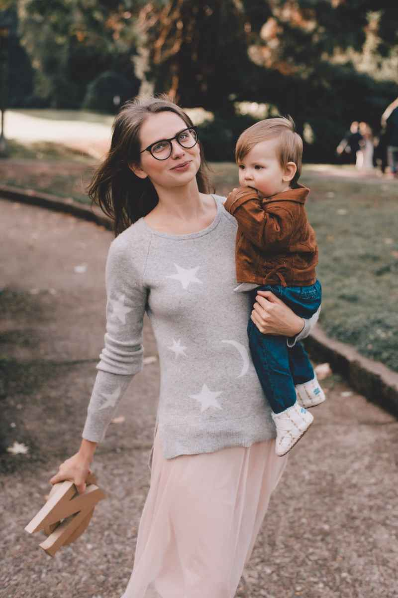 happy mother with son on arms in park