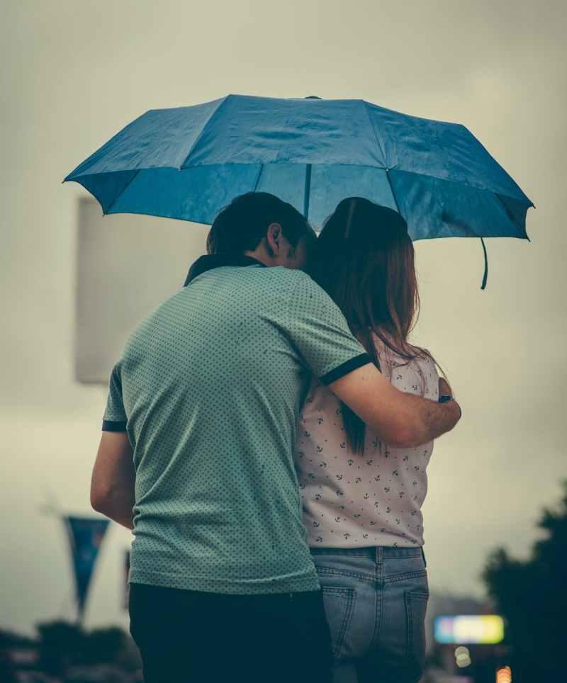 man hugging woman while holding umbrella
