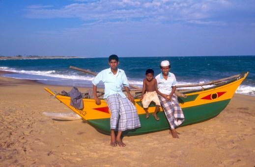 Sri Lanka, Hambantota, Jóvenes disfrutan de la conversación junto a una barca de pesca, retrato
