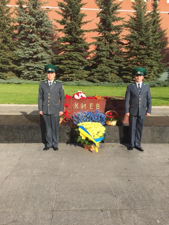 Посольство Украины в РФ украсило желто-синими цветами стелу Киева у стен Кремля и выставило там караул.