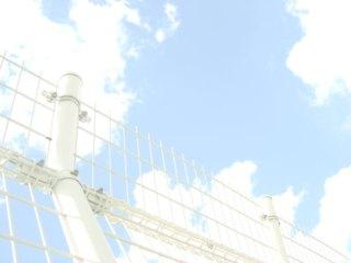 フェンス越しの空の写真素材