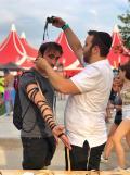 Az egyik fesztiválozó imaszíjat tesz Keszler Áron rabbinövendék segítségével