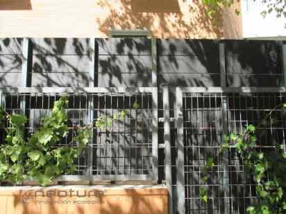 Cerramiento madera sintética. Instalación conservando el vallado metálico instalado previamente.