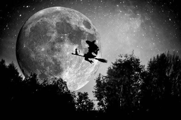 Witch on a broom flying in front of a full moon.