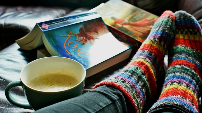 Feet up in rainbow socks next to mug of coffee and an open paperback book.