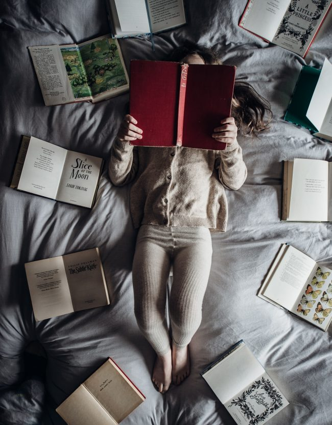Child lying on a bed reading a book, surrounded by more open books.