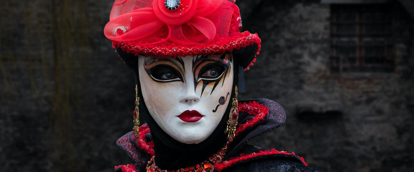 Woman in ornate red hat and beautiful clown makeup
