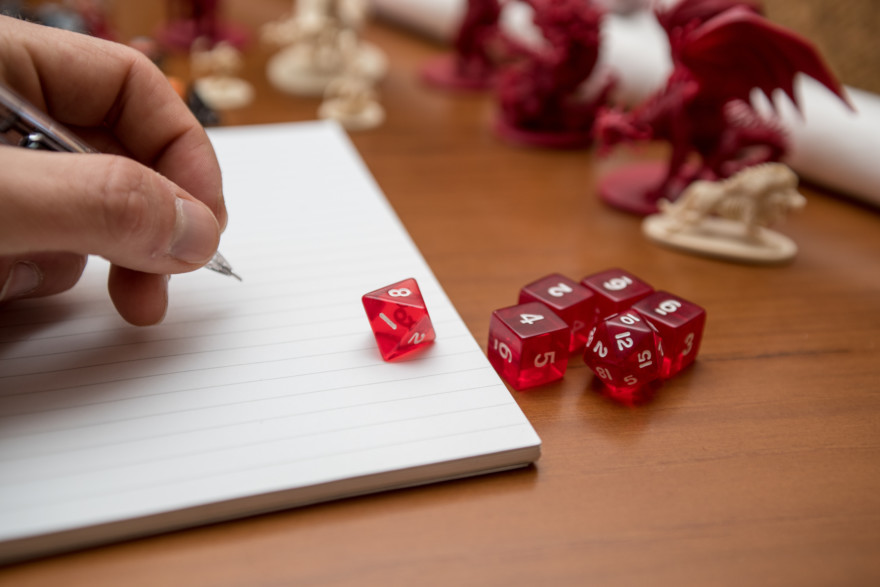 Pen, Notebook And Dices To Play Role Game Like Dungeons And Dragons. Writing With The Mechanical Pencil On The Notebook.