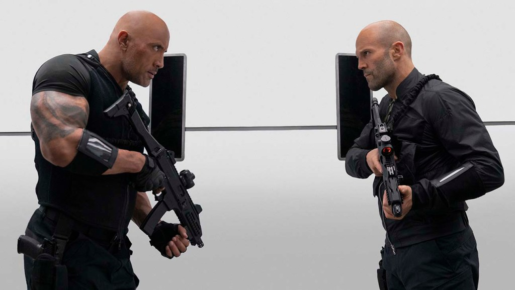 Hobbs and Statham facing one another with guns at the ready and threatening looks. Movie Review