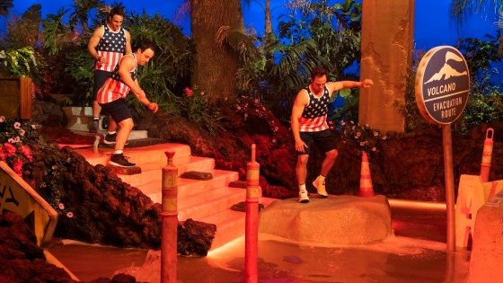 Three men in American flag T-shirts enter the obstacle course with water bathed in red light for Netflix's The Floor Is Lava