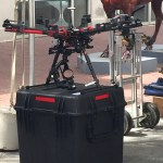 Commercial size remote controlled drone in black and red sitting on a crate.