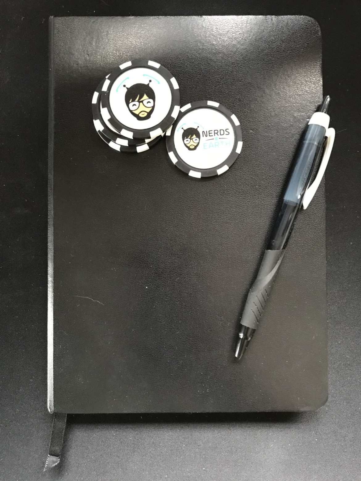 Abram's journal of game design, a little black book, complete with pen and Nerds on Earth poker chips.