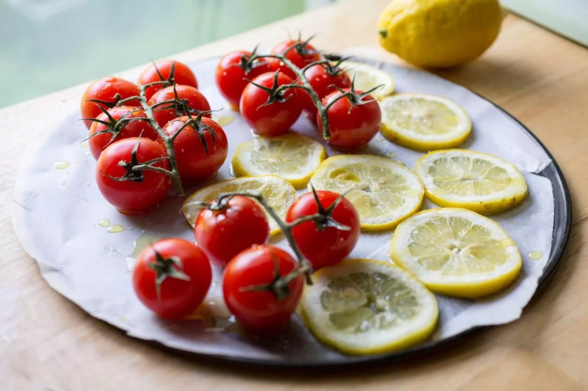 Tomatoes and lemon slices, ready for roasting.