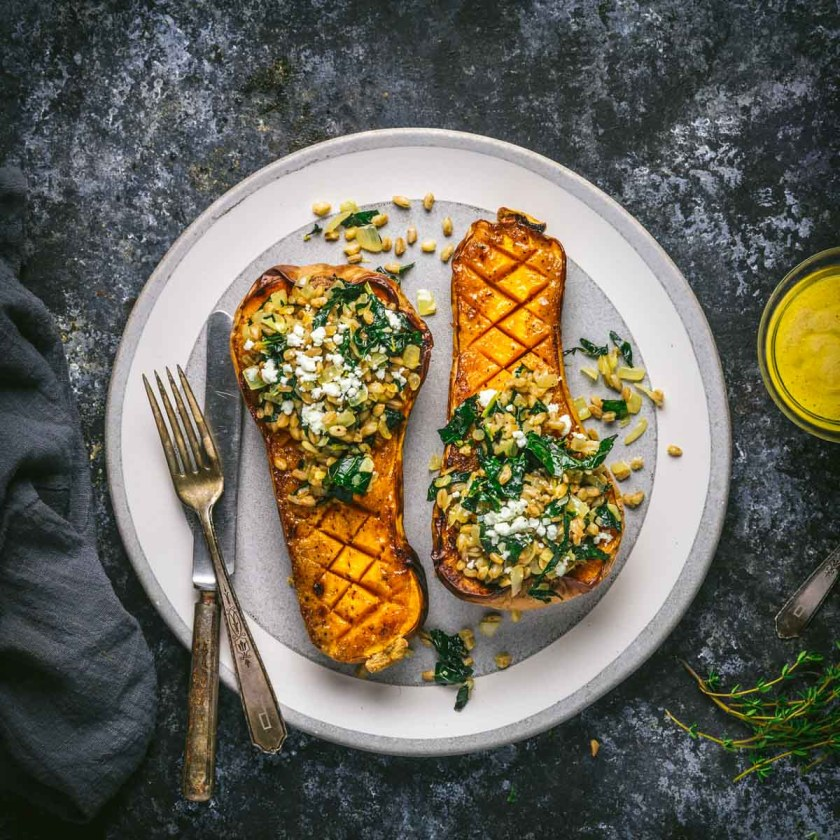 Butternut squash halves stuffed with greens and grains on a plate
