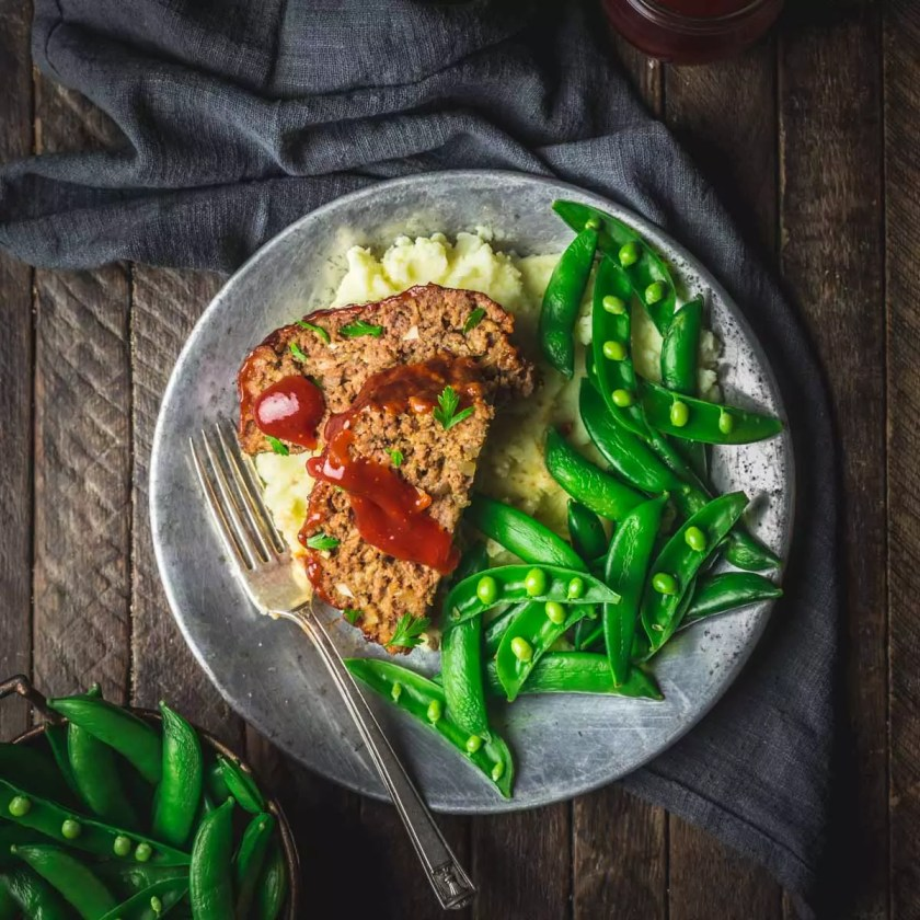 Meatloaf on a plate with sugar snap peas