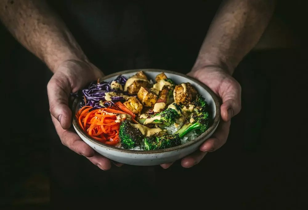 Hands holding a bowl with tofu, veggies and drizzled sauce