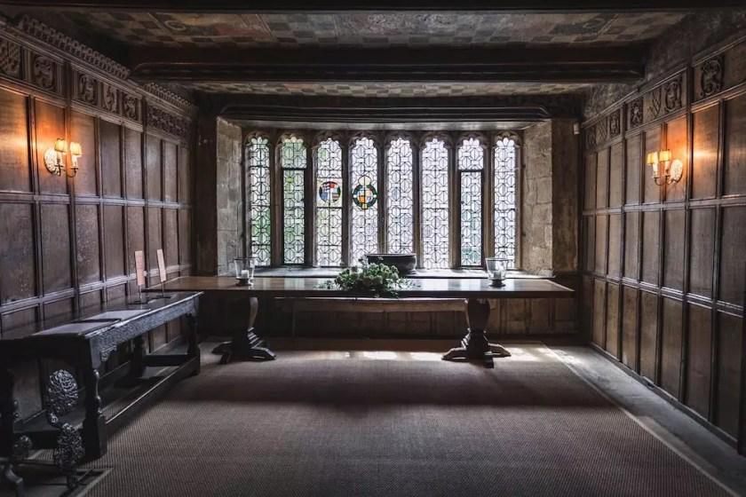 The wood-paneled interior of a Tudor mansion with stained glass windows in the background