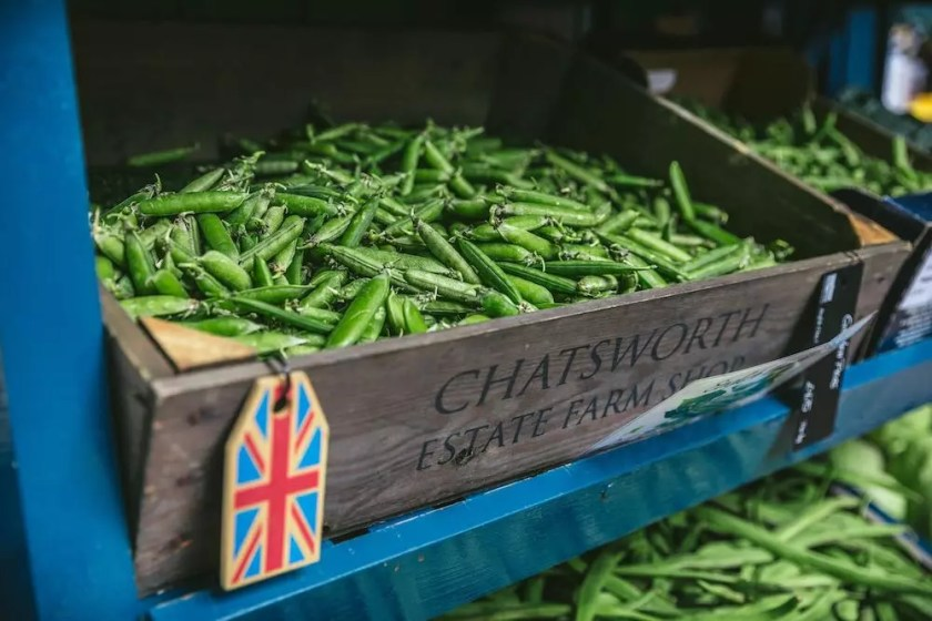 """A farmer's market shelf with a wooden box of snap peas. The label reads """"Chatsworth Estate Farm Shop"""""""