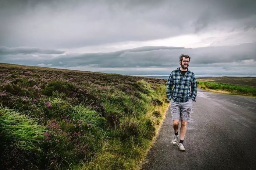 A wide, low moor with purple heather and a man walking towards camera