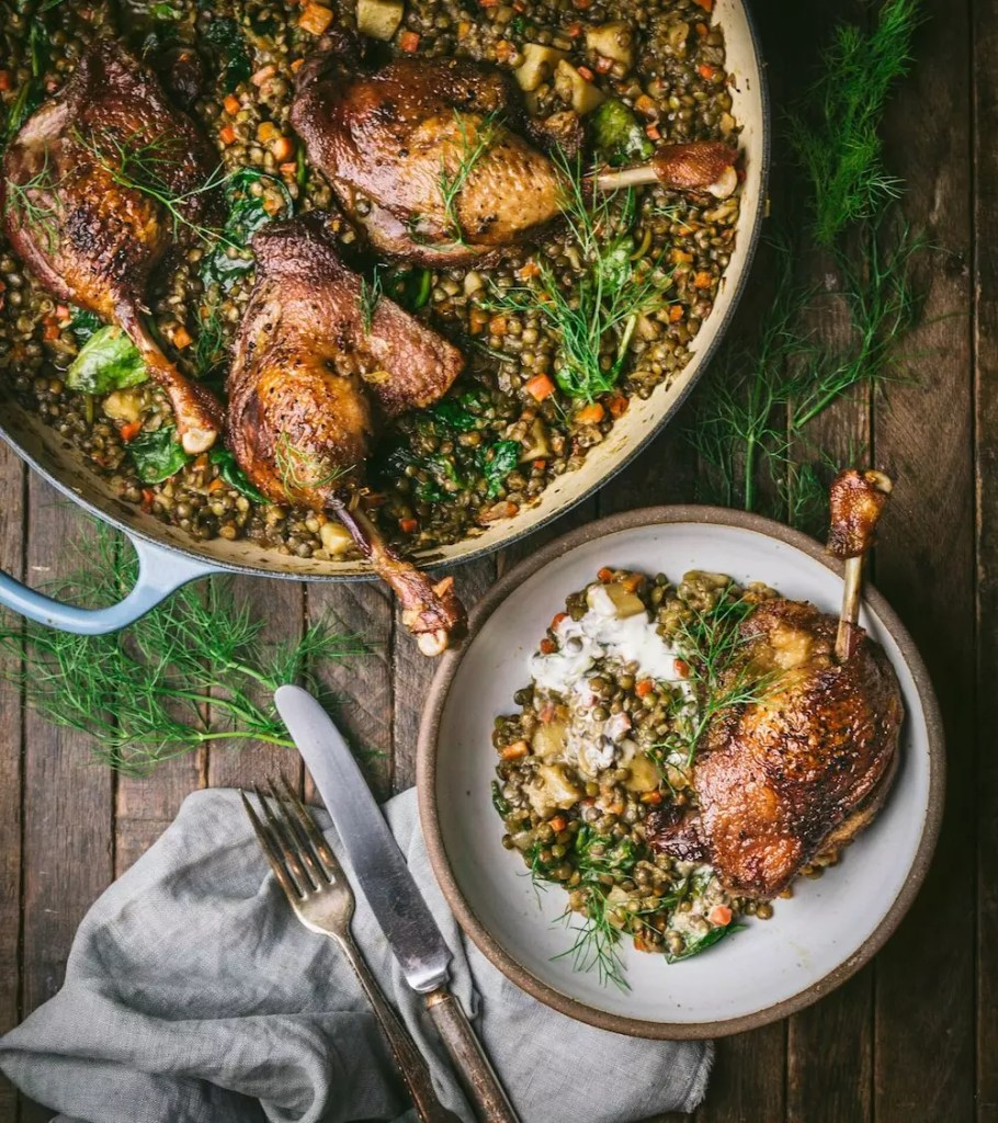 A braised and a small plate on a table, with cooked duck legs and lentils arranged in them