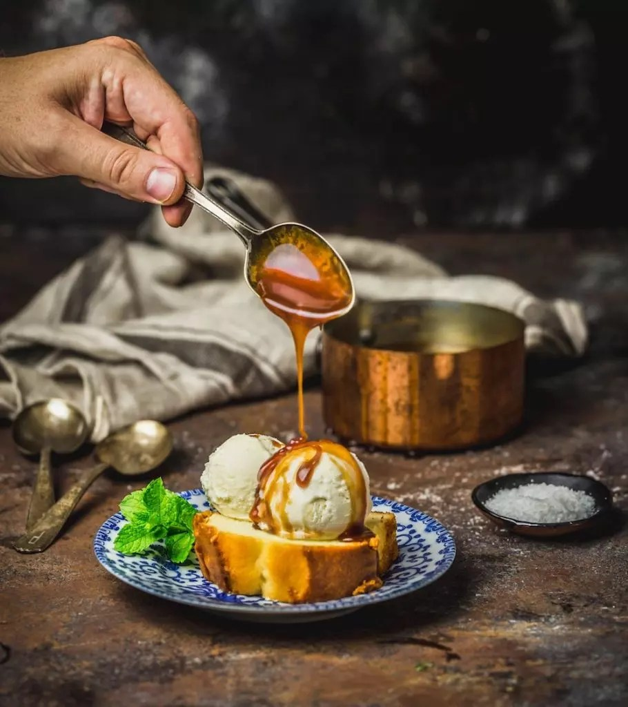 A hand pouring caramel from a spoon onto a bowl of ice cream and cake