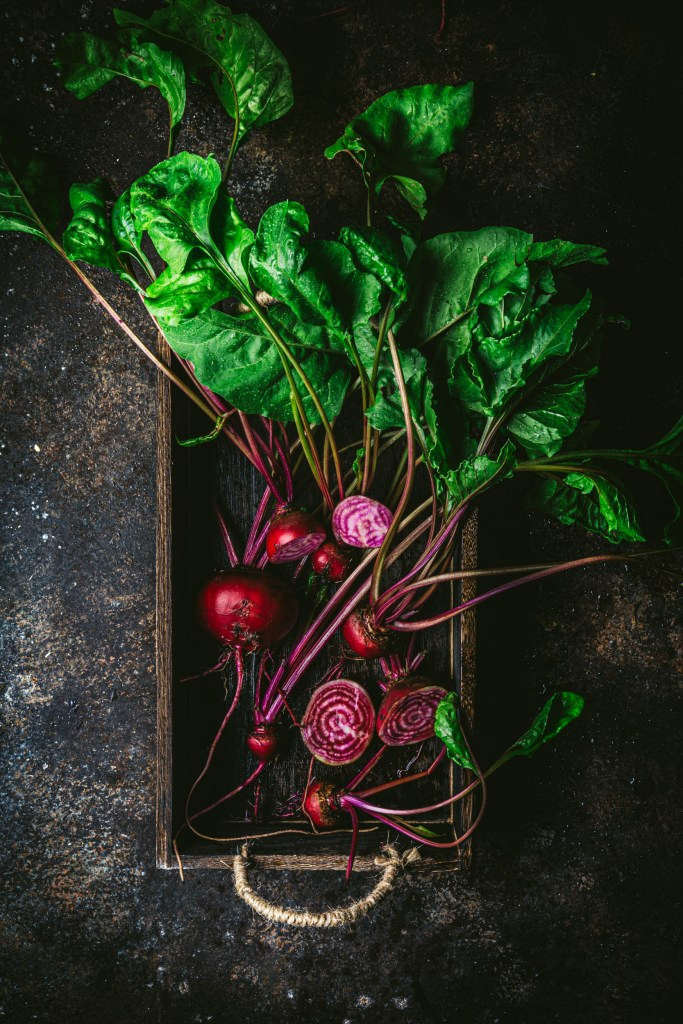 A bunch of beets in a wooden box