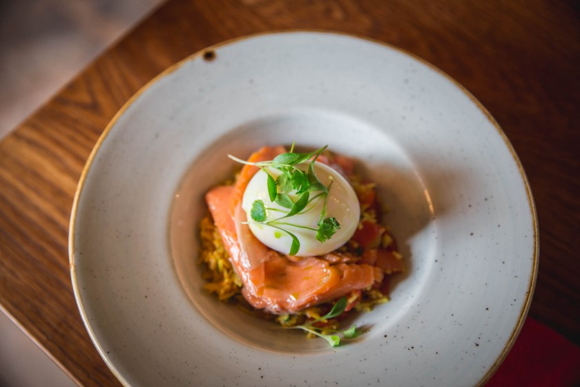 A  poached egg on a slice of smoked salmon in a bowl