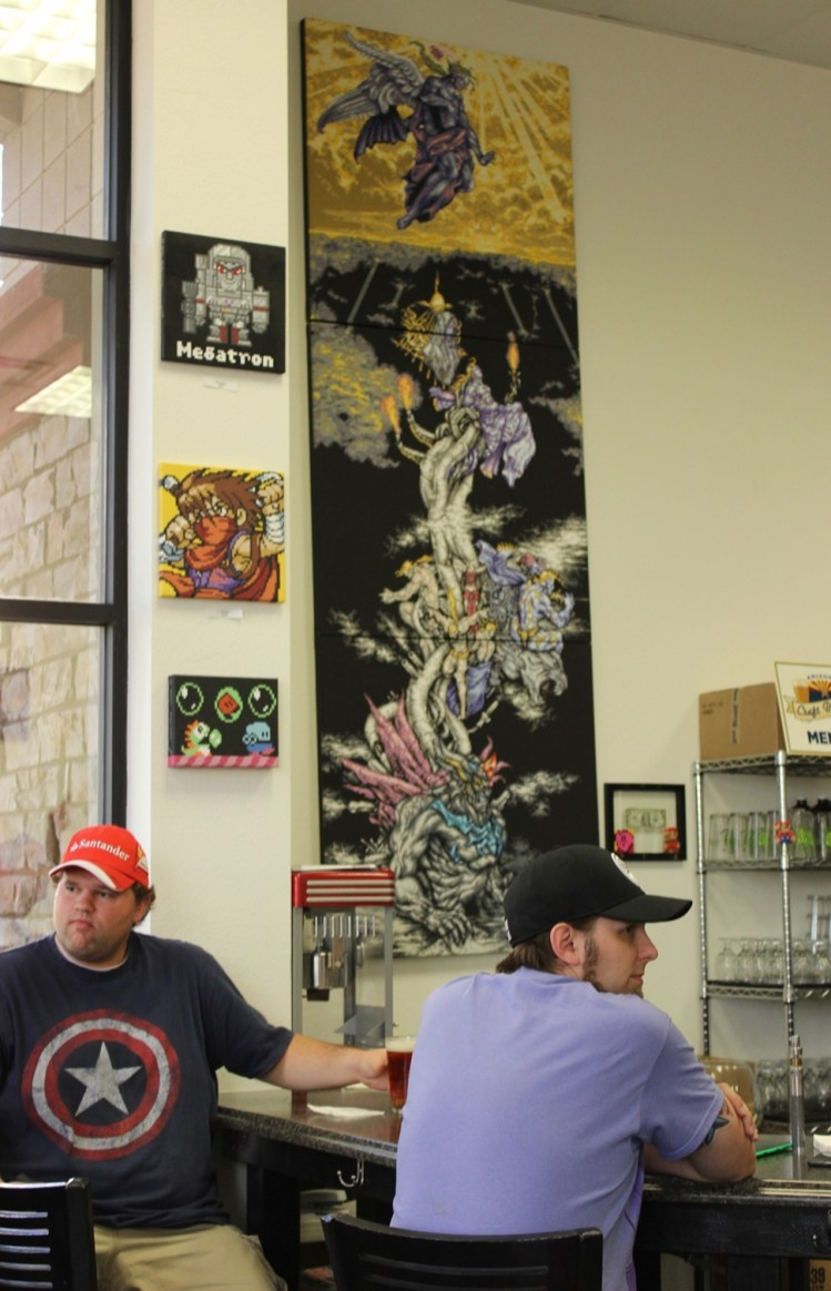 Two patrons sit at the bar alongside the huge Final Fantasy art piece.