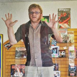 Comic creator Russ Kazmierczak in Drawn to Comic window (courtesy Susan Brown, Drawn to Comics.)