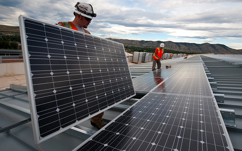 """Workers install photovoltaic panels on roof in this file photo. A new report says Phoenix gained solar capacity in the past year, but was outpaced by cities in other states that saw aggressive growth. (<a href=""""https://flic.kr/p/fozyTg"""" target=""""_blank"""">Photo</a> by Dennis Schoeder/<a href=""""https://www.flickr.com/photos/departmentofenergy/"""" target=""""_blank"""">Department of Energy</a>)"""