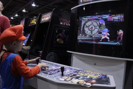 A young Mario cosplayer tries his best at Marvel vs. Capcom 2.