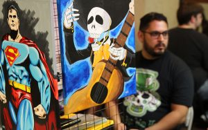 Hector Echevarria paints comic book characters and promotes his work online. He showed some of his work at Drawn to Comics in Glendale. (Photo by Maddy Ryan/Cronkite News)