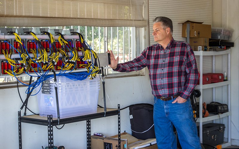 """Retiree Steve Irwin checks the temperature of his """"mining rig,"""" a set up of 14 computers that continuously solve algorithms to compete for cryptocurrency rewards. He said the computers make him $450 per day. (Photo by Jenna Miller/ Cronkite News)"""