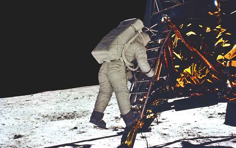APOLLO 11 ONBOARD PHOTO: ASTRONAUT ALDRIN MAKES FIRST STEP ONTO THE SURFACE OF THE MOON.