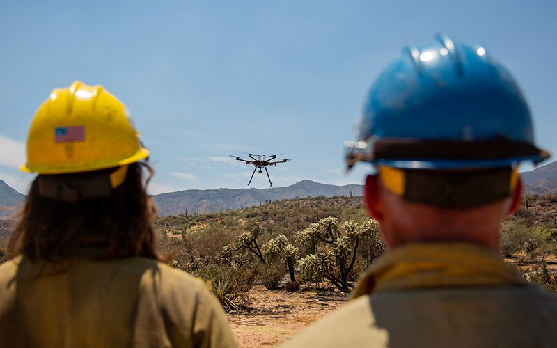 Pilot Chris Mariano (left, with aviation manager Gary Baumgartner) lands a Matrice 600 drone near the Woodbury Fire in June. (Photo by Anton L. Delgado/News21)