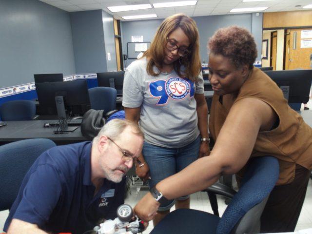 University of Memphis engineering professor Daniel Kohn (left) helps local science teachers Iris Myers (center) and Sonya Boyce program a robot during a robotics teacher training on campus. July 23, 2019.