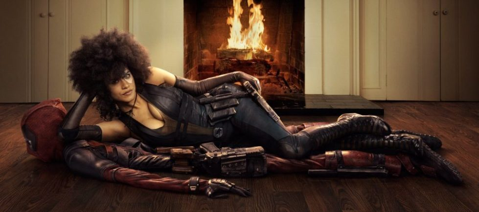 Zazie Beetz plays Domino, a deadly assassin. She likes in alluring fashion in front of a fireplace on a rug that appears to be made out of Deadpool's corpse